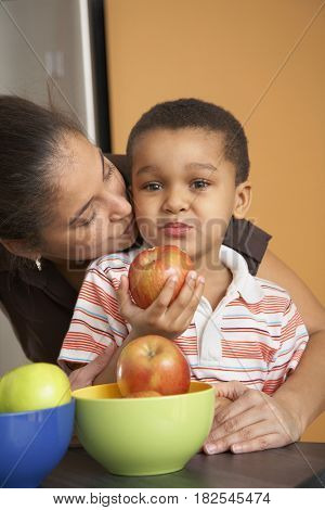 Dominican mother kissing son who's eating apple