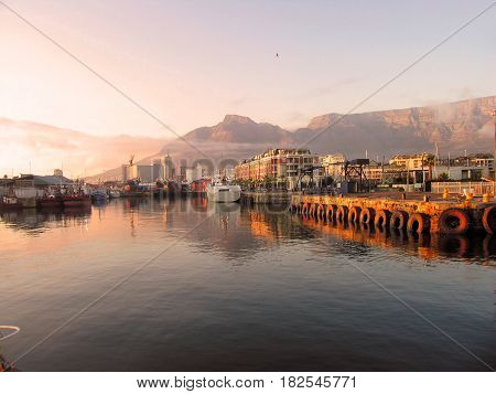 FROM CAPE TOWN, SOUTH AFRICA, SUN SETTING OVER VICTORIA AND ALFRED WATERFRONT.