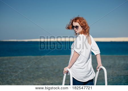 Beautiful ginger woman in sun glasses on a white yacht in a Red sea with clear turquoise water. Relaxation at summer vacation under a sun. Woman looks to the camera.