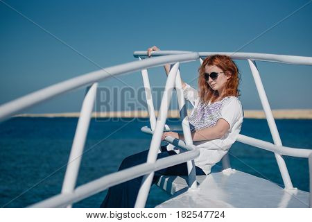 Beautiful ginger woman in sun glasses sits on a white yacht in a Red sea with clear turquoise water. Relaxation at summer vacation under a sun.