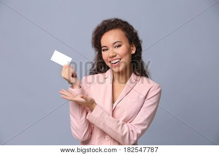 Beautiful African American woman with business card on grey background