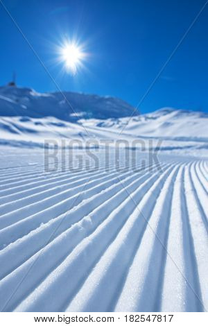 Snow path ski track surface corduroy texture selective focus