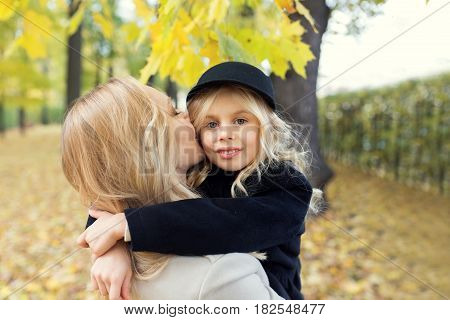 Blonde hair mother is holding her attractive daughter in her arms and giving her a kiss. They are at the park now full of trees and yellow leaves.
