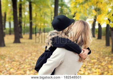 Blonde woman is hugging a little girl. We cant recognize their faces cause they turned away their fronts, This image was taken at the park. Obviously, its autumn season their due to faded trees around them
