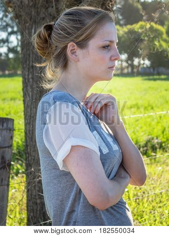 Portrait of serious young blonde woman looking ahead and away from camera standing in the shade under a tree in a rural setting - Vertical photo