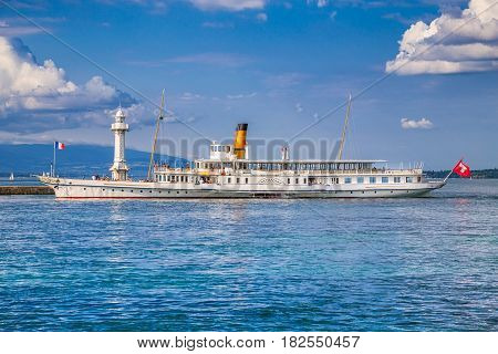 View of traditional paddle steamer excursion ship with historic Les Paquis Lighthouse on famous Lake Geneva on a sunny day with blue sky and clouds in summer Geneva Switzerland