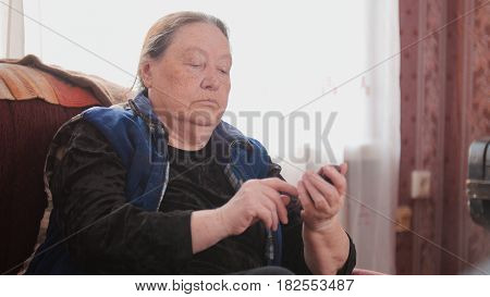 Old Woman pensioner speaks on cell phone, telephoto, cllose up