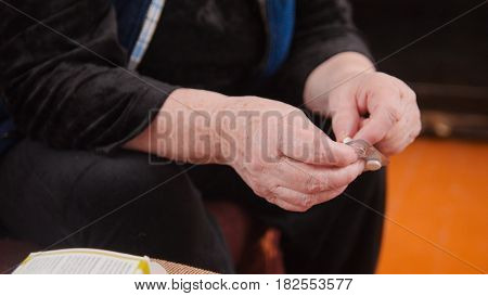 Hands of elderly woman with pills medication packages - pension healthcare, close up
