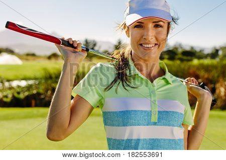 Beautiful Female Golfer Holding Golf Club On Field