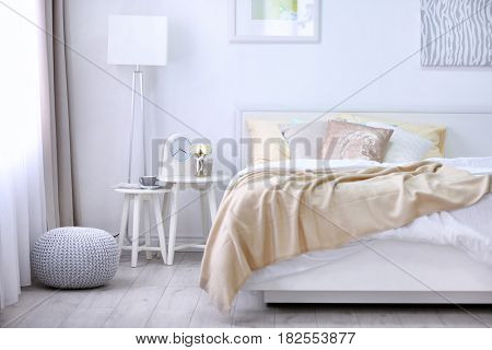 Comfortable bed with soft beige coverlet and pillows in light modern room