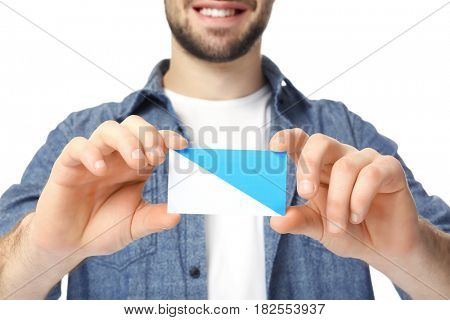 Handsome young man with business card on white background, closeup
