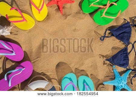 Summer beach fun - frame on sand with sandals and swimming suits