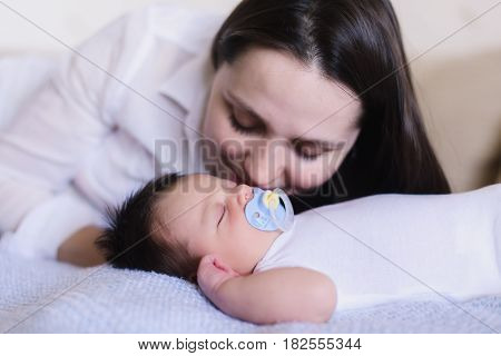 Newborn baby boy with mother. Baby sweet sleeping on a white bed. Child with a pacifier in his mouth. Mother kisses sleeping baby