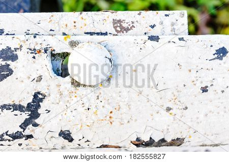 metal surface with old paint, some visible damage, as well as metal rivets and bolts connecting the sheets of material. Small depth of field