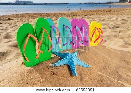 Summer beach fun - set of family sandals in sand on Las Teresitas beach, Tenerife, Canarias
