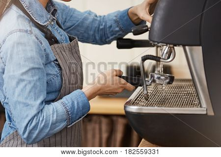 Closeup of female bartender in denim shirt and apron cleaning bottomless portafilter with steamer.