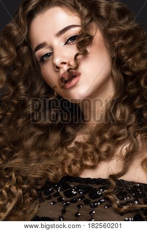 Beautiful brunette girl in move with a perfectly curly hair, and classic make-up. Beauty face. Picture taken in the studio on grey background.