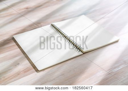 Blank notebook mock up on wood background.