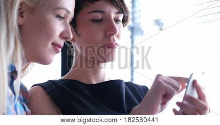 two business woman using cell phone in modern office bulding