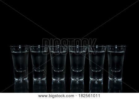 Shot glass with vodka on black background