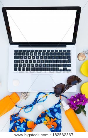 Summer beach fun mock up -laptop with swimming suit, sandals, sunglasses and sunscreens, copy space on blank screen