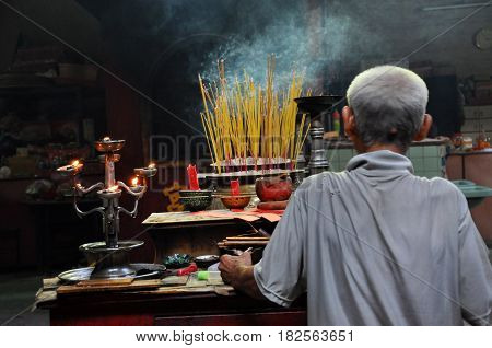 Asian People Praying And Burning Incense Sticks In A Pagoda