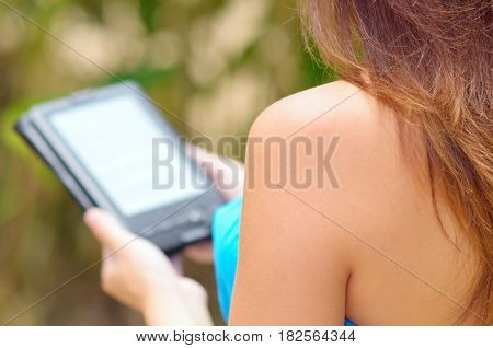 Young woman reading e-book in garden. Woman wearing blue dress.