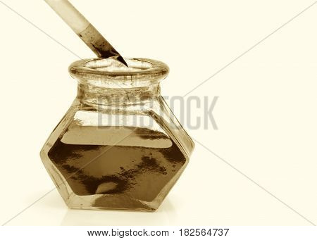 Quill pen and ink bottle close up image