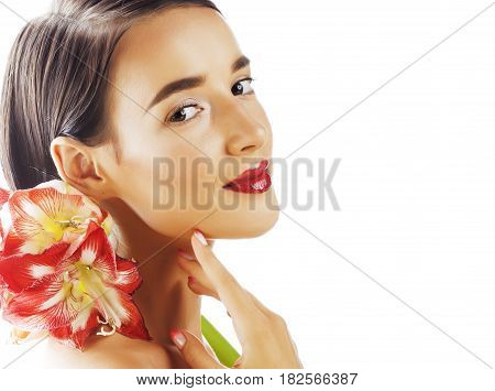 young pretty brunette real woman with red flower amaryllis close up isolated on white background. Fancy fashion makeup, bright lipstick, creative Ombre manicured nails