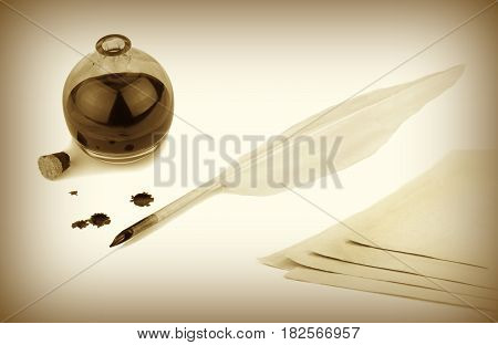 Quill pen, papers and ink bottle with ink blots