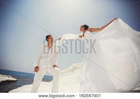 Wind Blows Bride's Dress While She Stands Behind A Groom On A Sea Shore