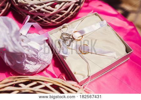 Rich golden wedding rings lie on the white ribbons in a silver box