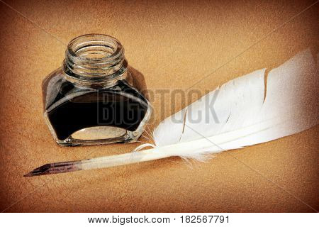 Quill pen and ink bottle on brown