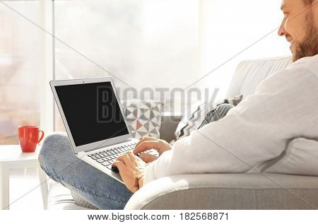 Handsome young man with laptop at home