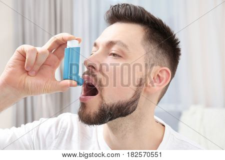 Young man using asthma inhaler at home