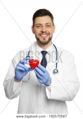Handsome doctor holding red plastic heart on white background