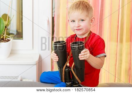 Childhood kids imagination concept. Concentrated little boy playing with binoculars having fun