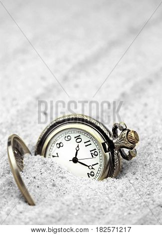 Antique pocket watch buried in sand .