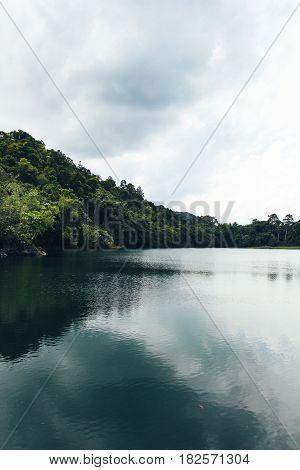 Dark reflective lake, green hill and cloudy skies.