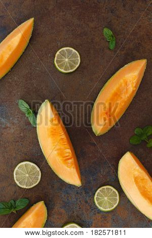 Cantaloupe melon slices and lime on rustic dark  background. Top view, copy space, flat lay