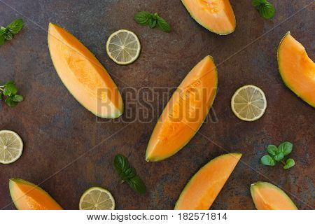 Slices of cantaloupe melon  and lime on rustic dark  background. Top view, copy space, flat lay