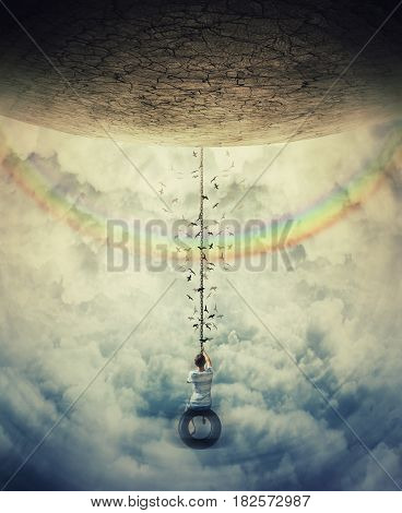 Young boy suspend on a tire swing in the clouds over the rainbow avoiding the gravitational force. Having fun and freedom concept.