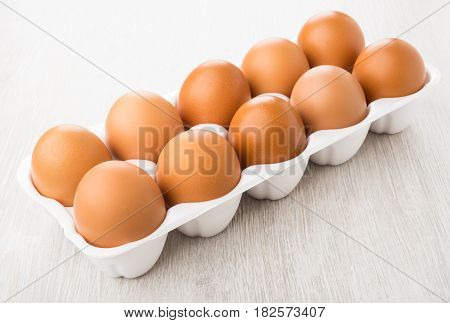 Plastic Container With Brown Chicken Eggs On Table