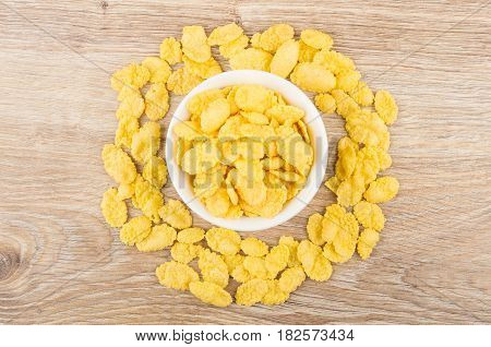 Corn Flakes In Glass Bowl And On Wooden Table