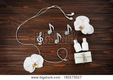 Spa music concept. Notes, earphones and products on wooden background