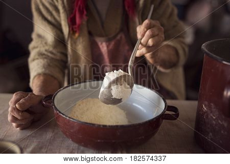 Detail of an elderly woman's hand holding a ladle and adding some flour into a bowl in preparation for making homemade pasta. Selective focus