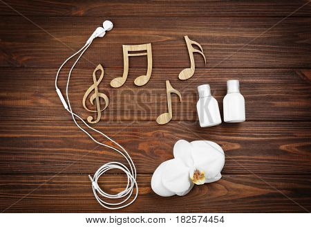 Spa music concept. Notes, earphones, orchid and cream bottles on wooden background