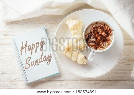 Sketchpad and cup of hot cocoa. Inscription in a notebook: Happy sunday
