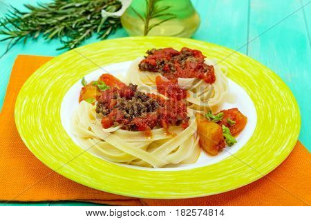 Pasta nest tagliatelle with bolognese sauce on a plate.