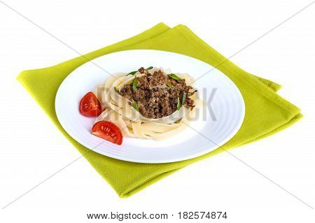 Pasta nest tagliatelle with bolognese sauce on a plate on green napkin isolated on white background.